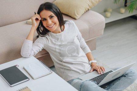 Photo pour Belle femme assise sur le sol, souriant et tenant ordinateur portable - image libre de droit