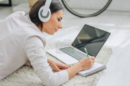 Foto de Hermosa mujer con auriculares acostados en el suelo y escribir en cuaderno - Imagen libre de derechos