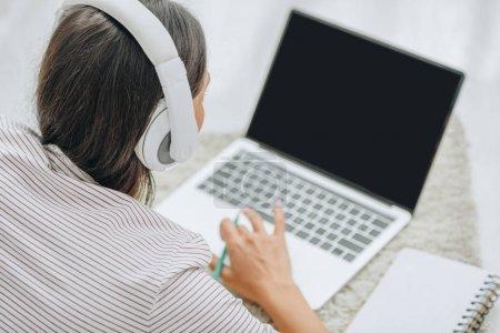 Photo pour Vue arrière de la femme avec écouteurs à l'aide d'un ordinateur portable et d'un crayon - image libre de droit