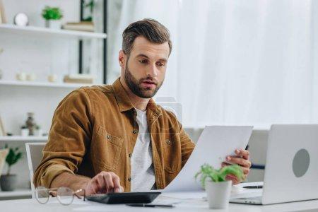 Photo pour Bel homme dans le papier de fixation de chemise et calculant avec la calculatrice - image libre de droit