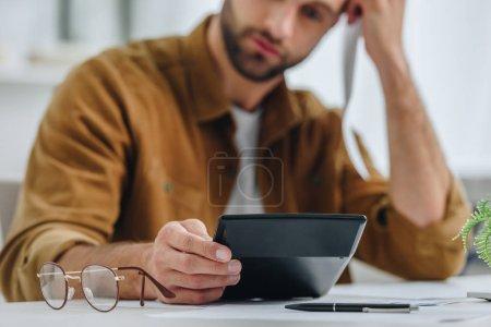 Photo pour Foyer sélectif de l'homme beau et triste dans la calculatrice de fixation de chemise - image libre de droit