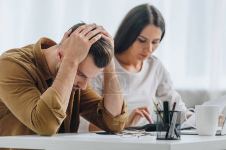 Photo for Sad and handsome man holding head and attractive woman using calculator - Royalty Free Image