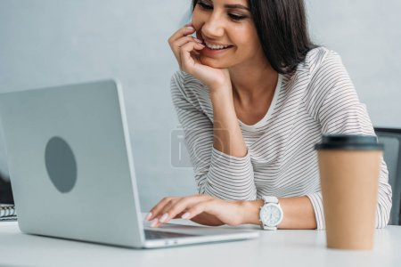 Photo for Attractive and brunette woman smiling and using laptop in apartment - Royalty Free Image