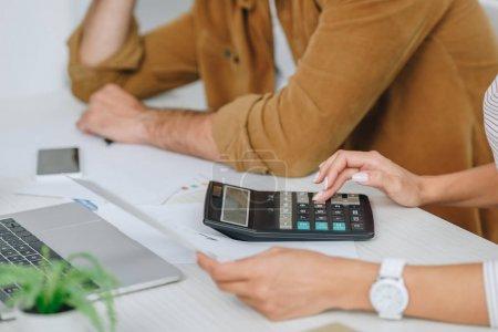 Photo pour Vue recadrée de l'homme et de la femme retenant le papier et utilisant la calculatrice - image libre de droit