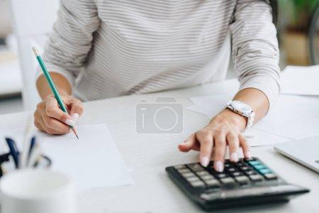 Photo pour Vue recadrée de la femme en utilisant une calculatrice et en écrivant au crayon - image libre de droit