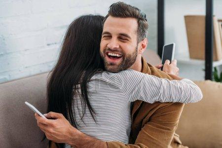 Photo pour Homme heureux et beau étreignant avec la femme et retenant le smartphone - image libre de droit