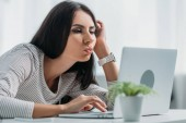 selective focus of beautiful and brunette woman using laptop and making faces