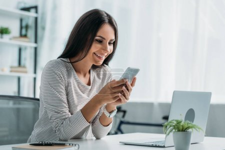 Photo for Attractive and brunette woman smiling and using smartphone in apartment - Royalty Free Image