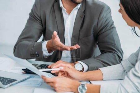 Foto de Cropped view of businessman and businesswoman woman in suits discussing document - Imagen libre de derechos