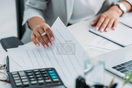 Photo pour Cropped view of woman doing paperwork and holding pencil - image libre de droit