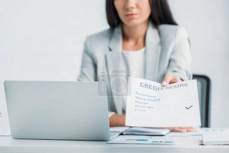 Photo pour Vue recadrée de la femme dans l'usure formelle tenant le pointage de crédit - image libre de droit