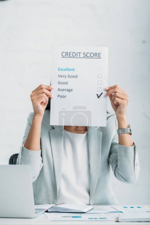 Photo for Woman in formal wear showing credit score at office - Royalty Free Image