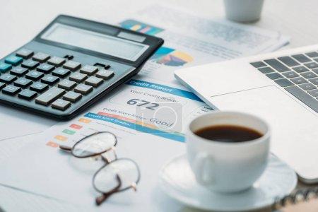 Photo pour Foyer sélectif de rapport de crédit, calculatrice, lunettes, tasse avec café et ordinateur portable - image libre de droit
