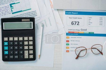 Photo pour Vue du haut du dossier de crédit, calculatrice, lunettes et crayon - image libre de droit