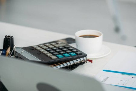 Photo for Selective focus of cup with coffee, calculator and notebooks - Royalty Free Image