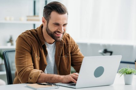 Photo for Handsome and happy man smiling and looking at screen of laptop - Royalty Free Image