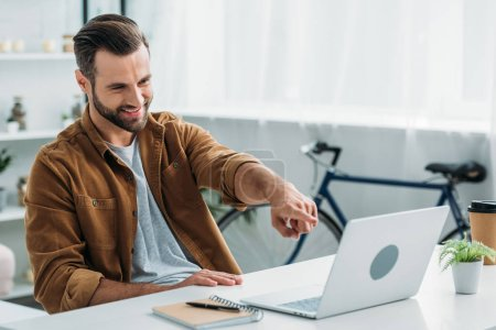 Photo for Handsome and happy man smiling and pointing with finger at screen of laptop - Royalty Free Image