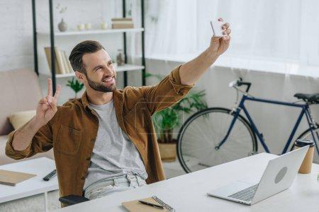 Photo pour Homme beau et heureux souriant, prenant le selfie et affichant le signe de paix - image libre de droit