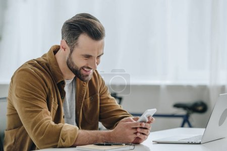 Photo for Handsome and happy man smiling and using smartphone - Royalty Free Image