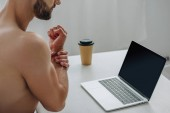 """Постер, картина, фотообои """"cropped view of man showing his hand in front of laptop """""""