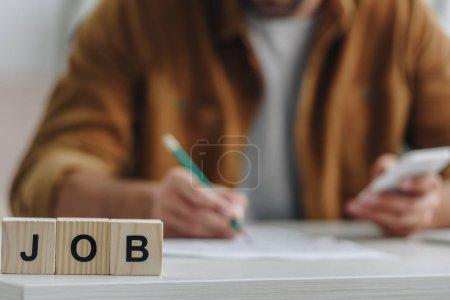 Photo pour Vue recadrée des cubes en bois avec le travail de lettrage et l'homme sur le fond - image libre de droit