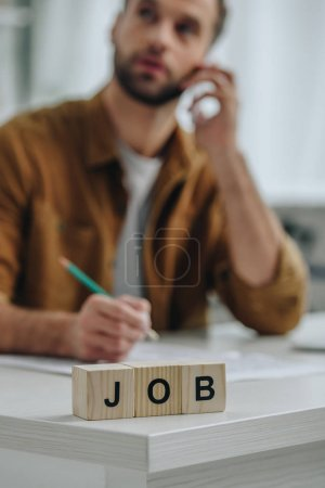 Photo for Selective focus of wooden cubes with lettering job and man talking on smartphone on background - Royalty Free Image