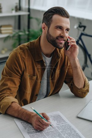 Foto de Handsome man talking on smartphone and holding pencil in apartment - Imagen libre de derechos