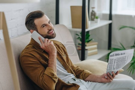 Photo for Handsome man talking on smartphone and holding newspaper in apartment - Royalty Free Image