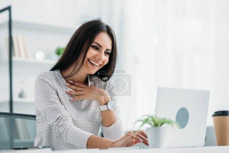Photo pour Femme heureuse et attrayante souriant et regardant l'écran de l'ordinateur portable - image libre de droit
