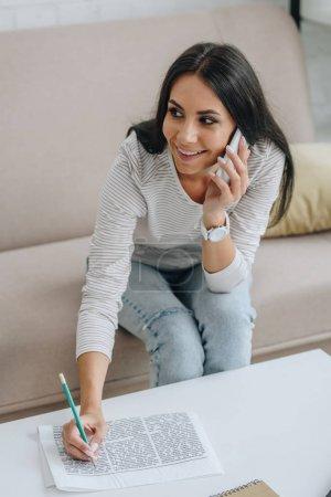 Photo pour Femme attirante et brune parlant sur le smartphone et retenant le crayon - image libre de droit