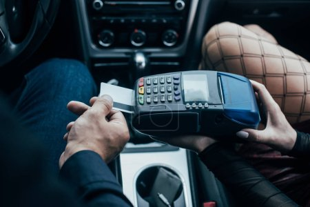 Photo for Top view of client paying by credit card near prostitute in car - Royalty Free Image