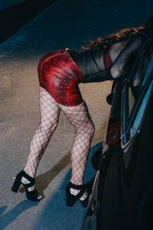 cropped view of prostitute in red skirt and stockings standing near car