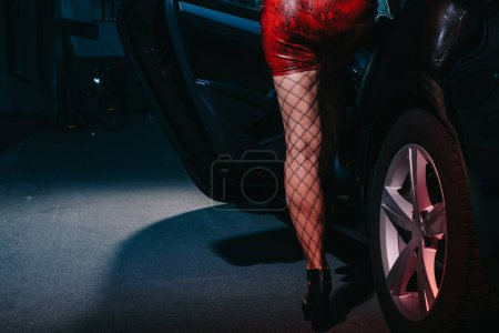 cropped view of woman in red skirt standing near car door while sitting in car