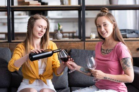Photo pour Deux lesbiennes tenant des verres à vin et versant du vin tout en s'asseyant sur le sofa dans le salon - image libre de droit