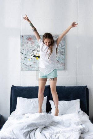 Photo for Full length view of happy tattooed girl jumping on bed in bedroom - Royalty Free Image