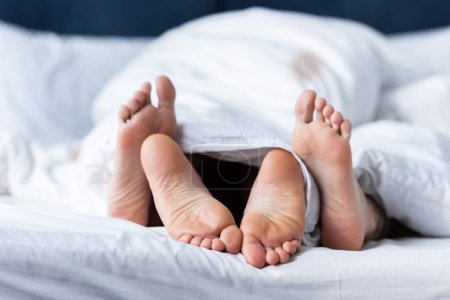 Photo pour Vue partielle de deux lesbiennes pieds nus couchées sous la couverture - image libre de droit
