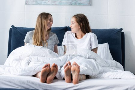 Photo pour Deux lesbiennes pieds nus souriantes assises sur le lit et se regardant - image libre de droit