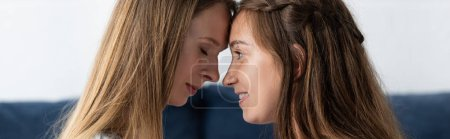 Photo for Panoramic shot of two lesbians touching foreheads at home - Royalty Free Image