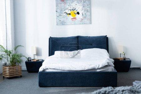 Foto de Acogedor dormitorio moderno con cama y planta verde - Imagen libre de derechos