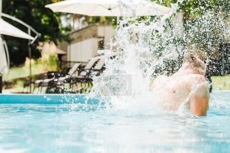 Photo pour Foyer sélectif de l'homme dans la piscine près de éclaboussures d'eau - image libre de droit