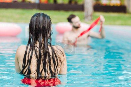 Photo pour Vue arrière de la femme nageant dans la piscine près de l'homme - image libre de droit