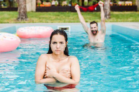 Photo for Selective focus of woman covering breasts in swimming pool near man - Royalty Free Image