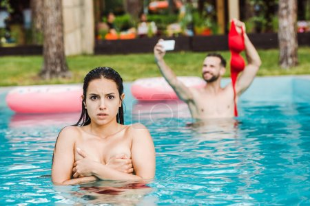 Photo for Selective focus of shocked woman covering breasts in swimming pool near man - Royalty Free Image