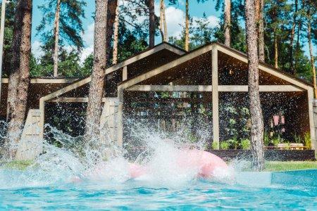Photo pour Éclaboussure près des anneaux gonflables dans la piscine avec de l'eau bleue propre - image libre de droit