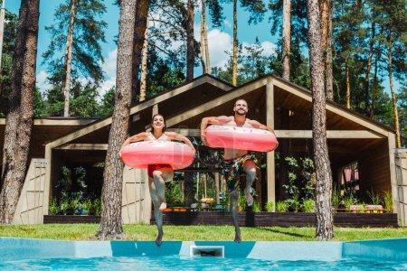 Photo pour Homme et femme gais avec anneaux gonflables sautant dans la piscine - image libre de droit