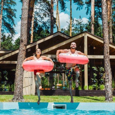 Photo pour Femme gaie et homme avec des anneaux gonflables sautant dans la piscine - image libre de droit
