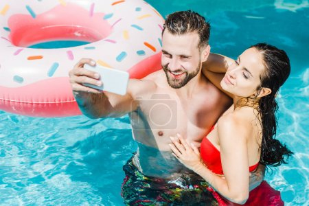 Photo for Overhead view of bearded shirtless man taking selfie on smartphone near attractive woman - Royalty Free Image