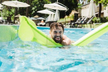 Photo pour Homme nageant avec matelas gonflable montrant la langue dans la piscine - image libre de droit