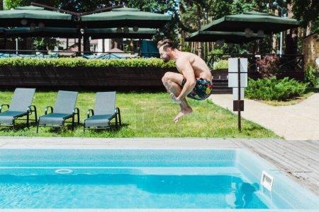 Photo pour Vue latérale de l'homme barbu avec saut pieds nus dans la piscine - image libre de droit