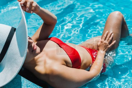 Photo for Young woman in stylish straw hat and red swimsuit near swimming pool - Royalty Free Image